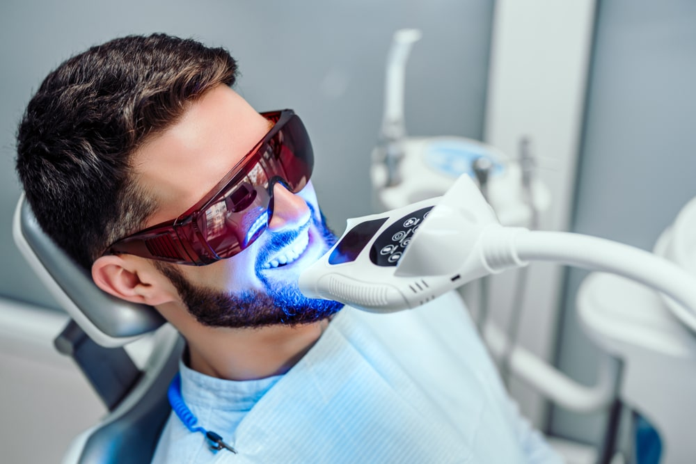 hombre joven sometiéndose a un blanqueamiento dental con luz led