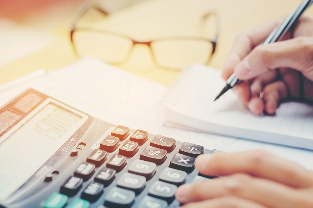 manos de hombre utilizando una calculadora y un bloc de notas