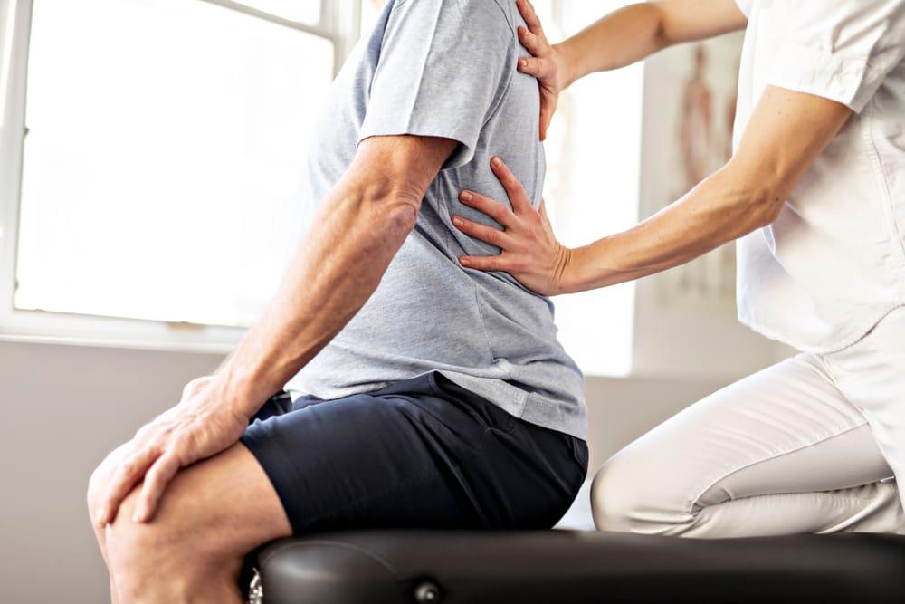 fisioterapeuta-ayudando-paciente-espalda
