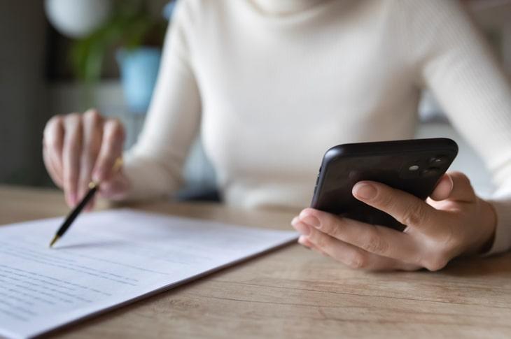Mujer leyendo un formulario sobre papel con un smartphone en una mano
