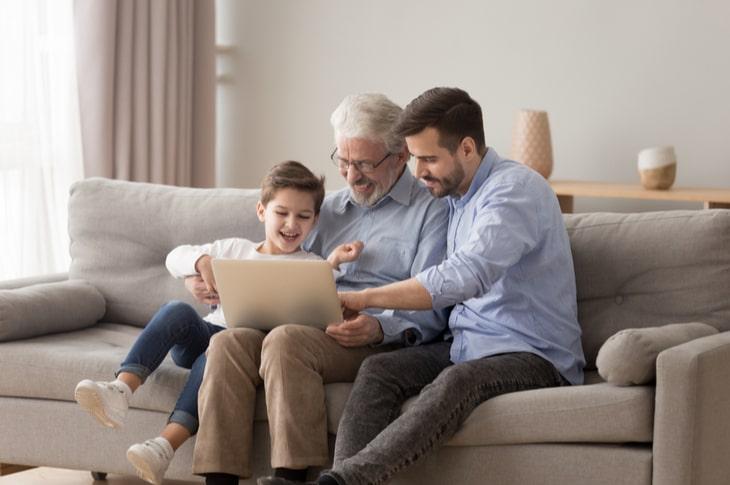 Abuelo, hijo y nieto sentados en el sofá con un portátil