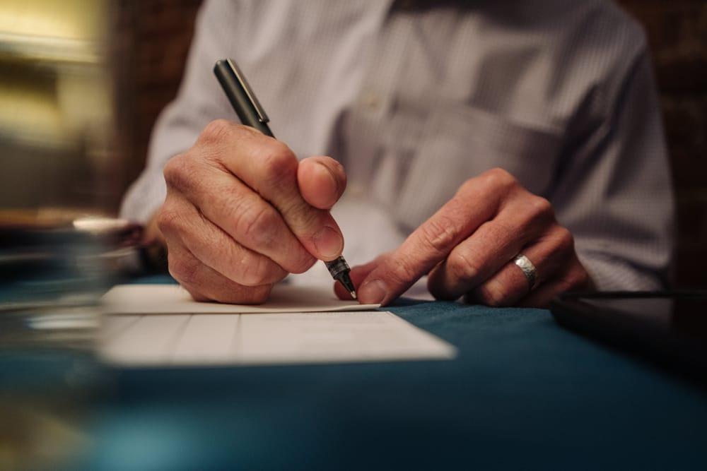 manos-firmando-papel-pluma