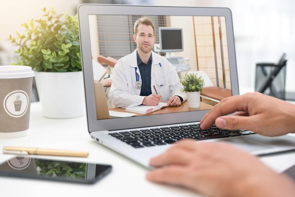 Doctor con ostetoscopio en pantalla de portátil en modo videoconsulta
