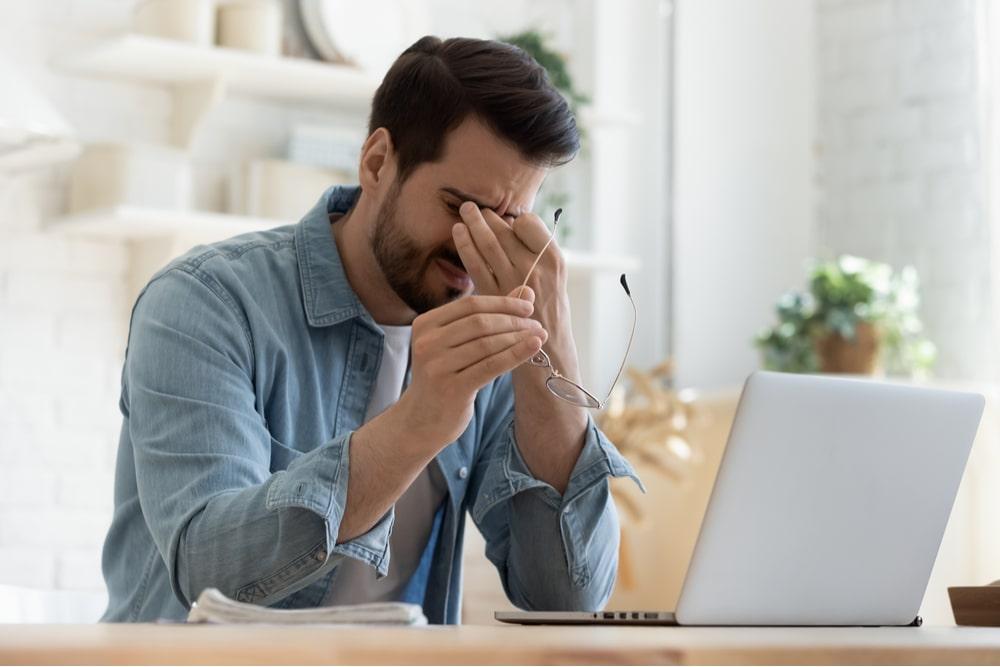 Joven cansado frotándose los ojos frente al ordenador con las gafas quitadas