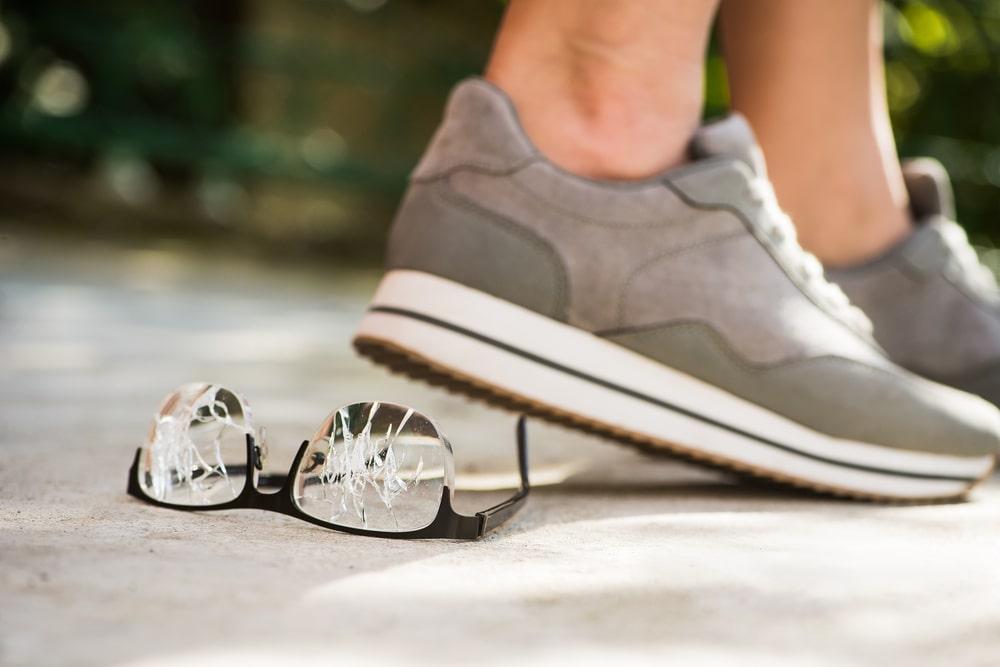 Gafas con cristales rotos en el suelo pisadas por unos pies con zapatillas deportivas grises