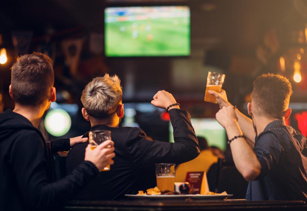 Tres hombres ven el fútbol en un bar