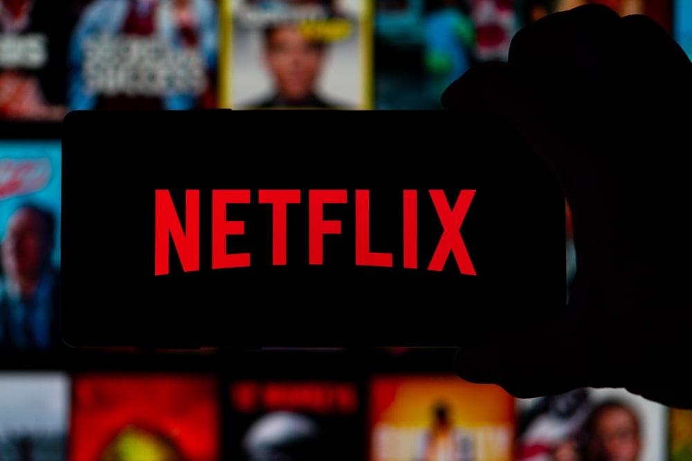Logo de Netflix con fondo negro con contenidos de fondo