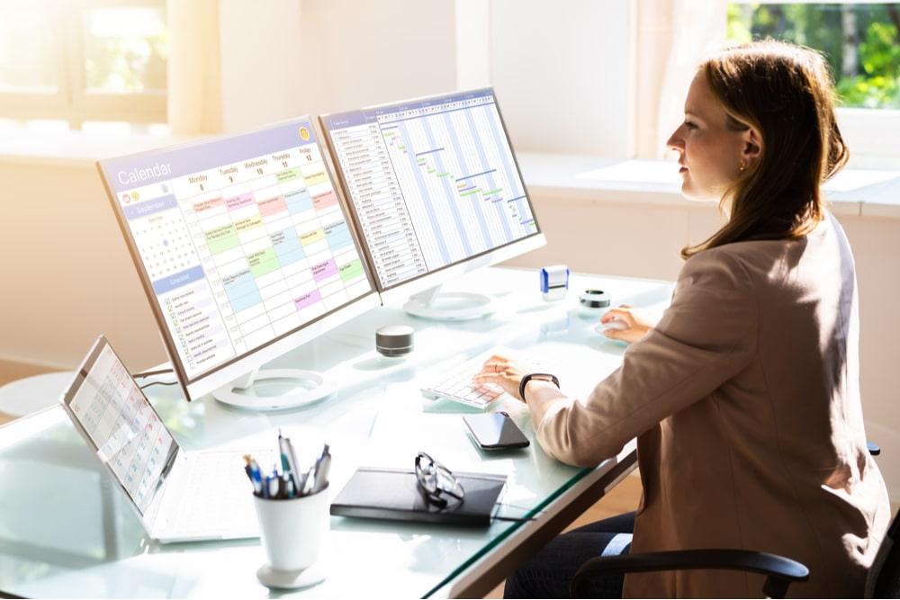 Mujer trabajando con un ordenador portátil conectado a dos monitores