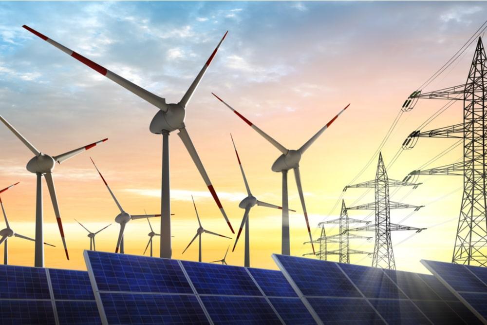 Parque eólico, placas solares y líneas de alta tensión sobre horizonte crepuscular