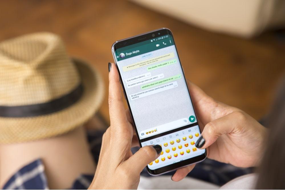 Mujer joven con uñas negras chateando en Whatsapp