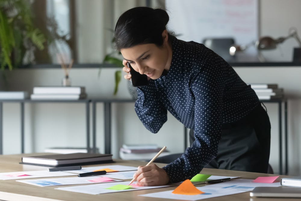 Mujer hablando por teléfono inclinada sobre un escritorio lleno de papeles