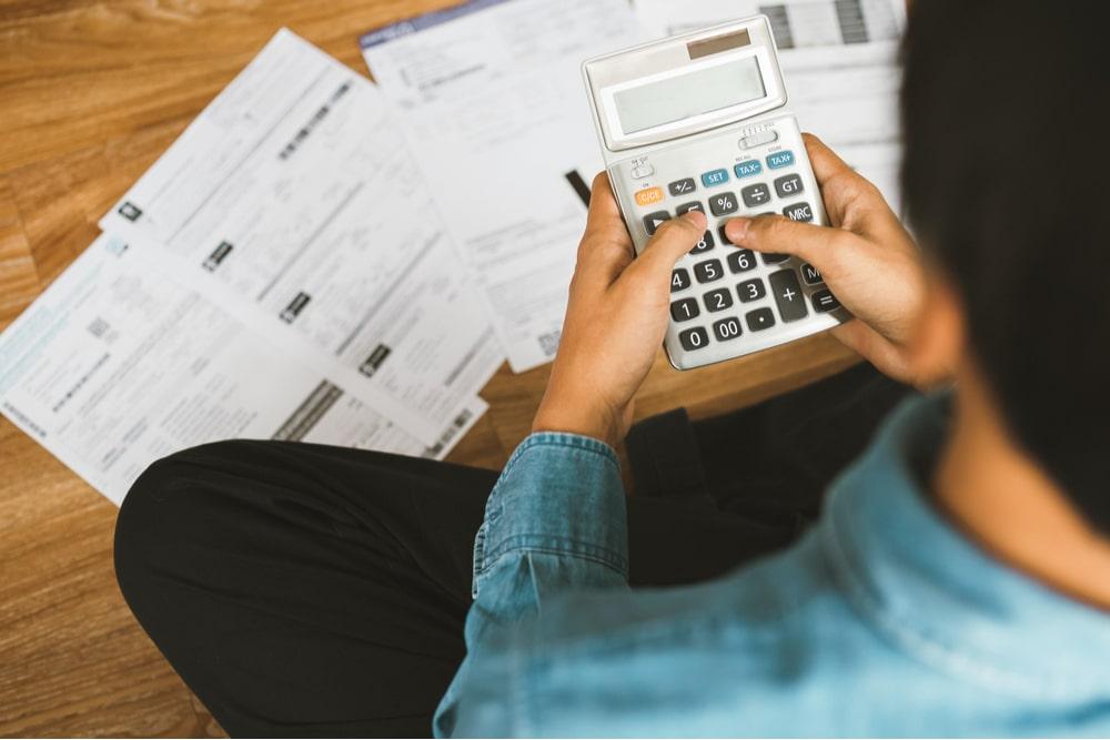 Hombre joven sentado sobre el suelo con las piernas cruzadas sobre un montón de papeles usando una calculadora