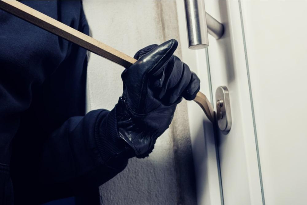 Ladrón con guantes negros forzando puerta con una palanca