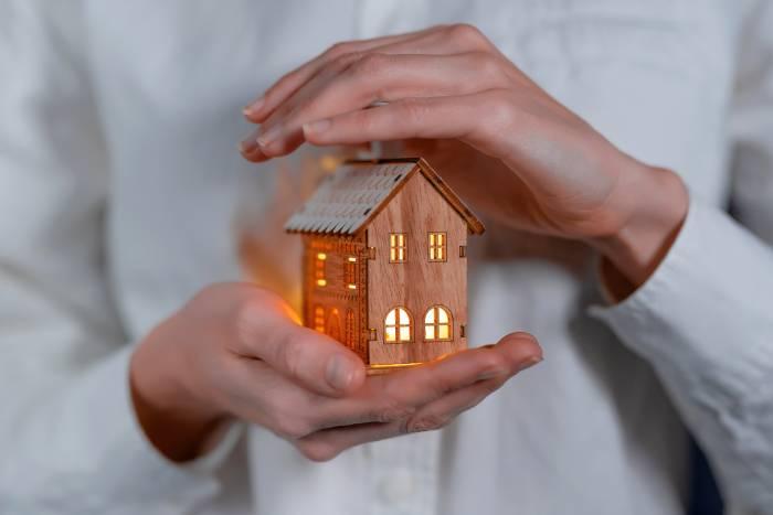Una mujer rodea con las manos una casa pequeña de juguete