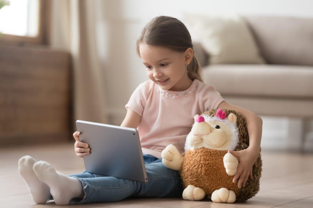 niña con peluche de erizo jugando con una tablet en el salón