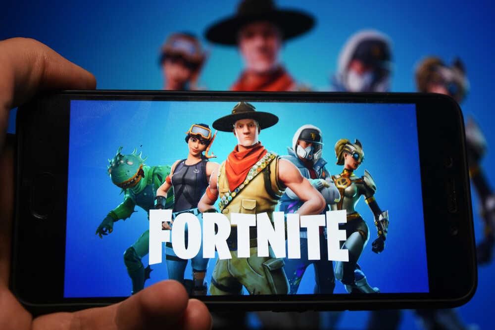 Mano sujetando un smartphone con Fornite en pantalla y background