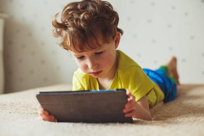 Niño en una cama con una tablet