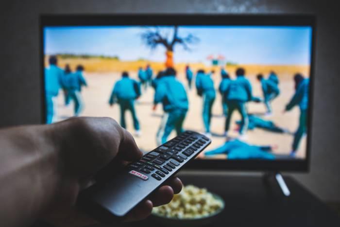 Pantalla de televisión emitiendo El juego del calamar (Netflix) y mano con mando de tv en primer plano
