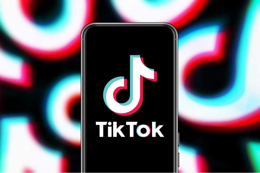 Logo de TikTok en pantalla de smartphone y multilogo en background
