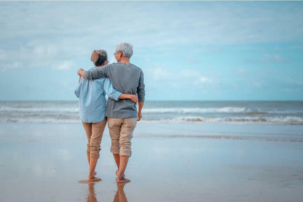 Pareja de ancianos caminando en la playa