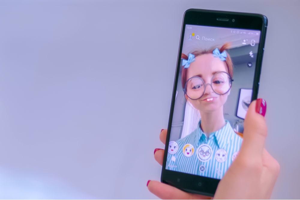 Mano de mujer sujetando un smartphone con un filtro de realidad aumentada
